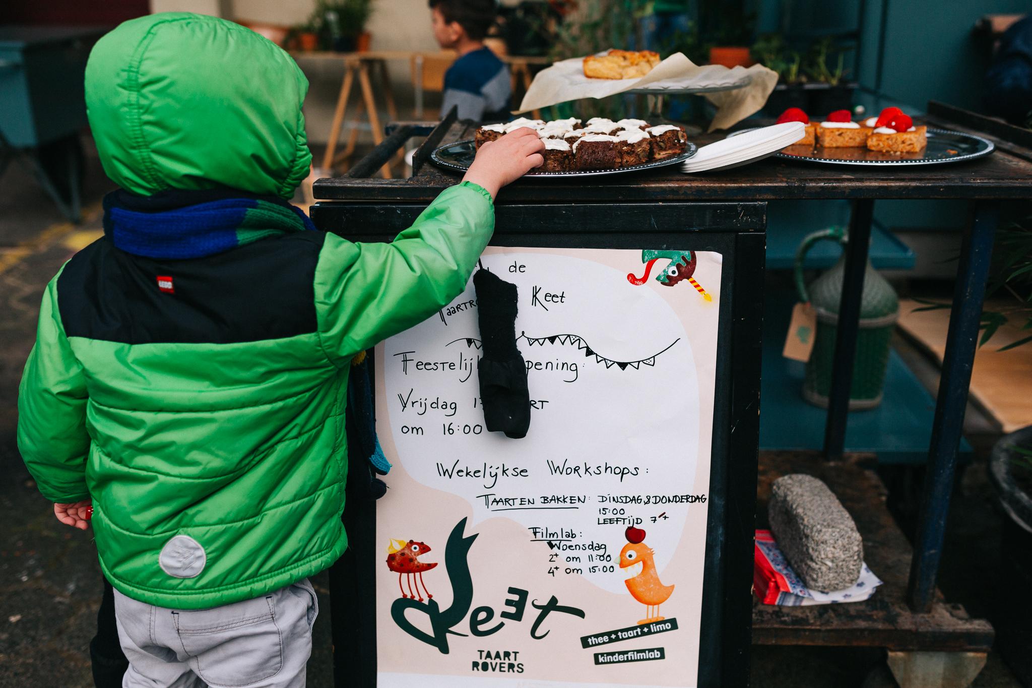Een kindje met een groene jas pakt van een schaal met taartjes